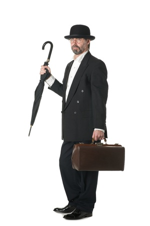 Middle aged businessman in a retro business suit with a bag and umbrella. photo
