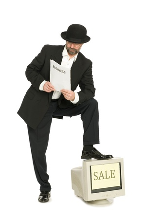 Man dressed as retro style reading a newspaper and sell old computer. Fun. Stock Photo - 10407804