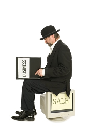 Middle-aged businessman in a suit retro style of sits and reads a book about business. photo
