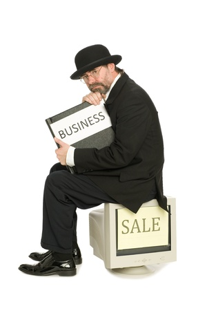 Thoughtful businessman wearing a suit retro sits on the old computer with a book of business. Stock Photo - 10407814