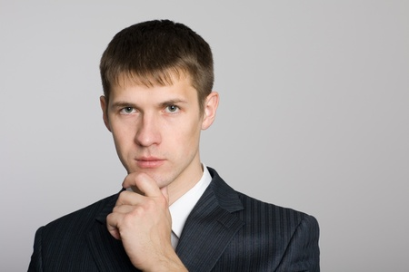 Pensive handsome young businessman. Isolated on white. photo