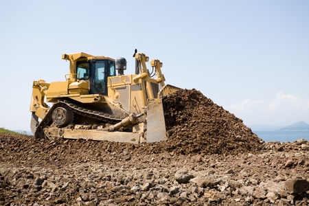 flatten: The bulldozer on a building site.On a background the sea. Stock Photo