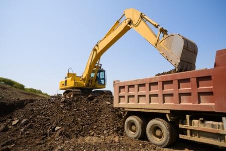 earthen: The excavator loads a truck an earthen ground