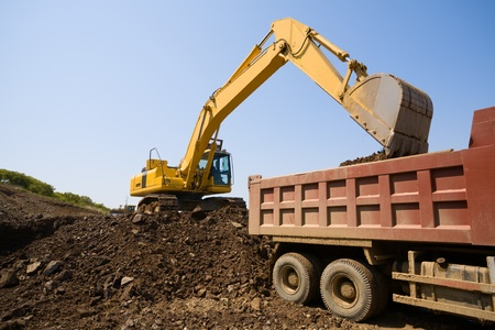 loads: The excavator loads a truck an earthen ground