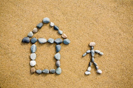 pictogram  of a house & person from a pebble on sand. photo