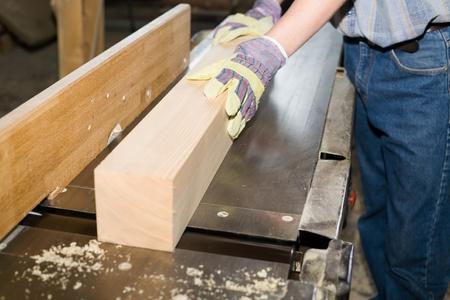 Een timmerman (sawman) werkt op de houtbewerking machine.