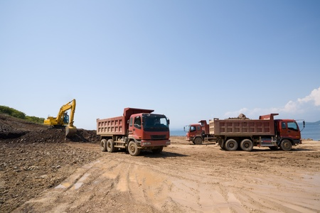 loads: Construction of new seaport.Excavator loads a dump truck an earthen ground