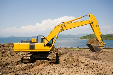 Excavator on the workplace on a background of the sea. Stock Photo