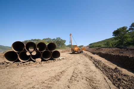 trench: Construction of a new oil pipeline.Machine to twist pipes(pipelaying crane) in a pipeline construction. Stock Photo