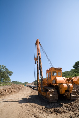 Construction of a new oil pipeline.Machine to twist pipes(pipelaying crane) in a pipeline construction. photo