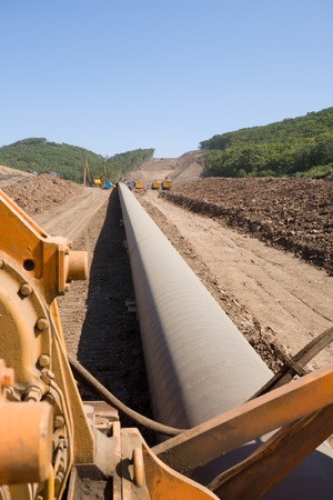 oilfield: Construction of a new oil pipeline.Machine to twist pipes(pipelaying crane) in a pipeline construction. Stock Photo