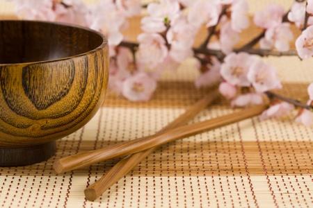 Wooden bowl(platter) and chopsticks on a bamboo mat.Backround cherry flowers.