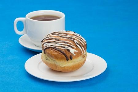 Donut(doughnut) with raisin covered with chocolate and sugar glaze. Cup tea.