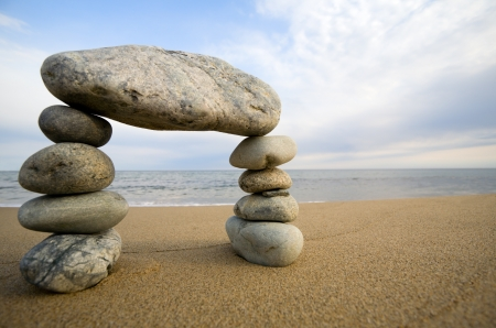 sand stone: Abstract triumphal arch from a natural stones on a background of the sea