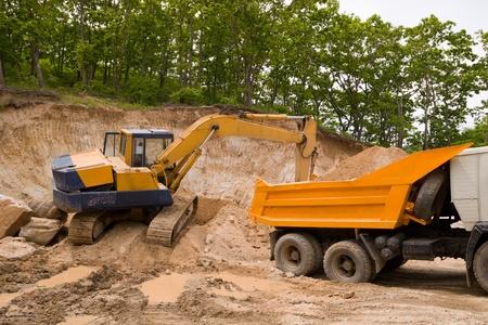 Excavator loads a truck an earthen ground photo