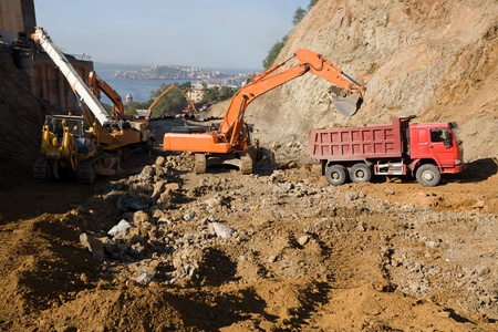sand quarry: Construction of road in the middle cities.To quarry.On a background the sea & town. Stock Photo