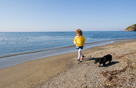 curly headed: The little girl walks at the sea with a dog.Spring.