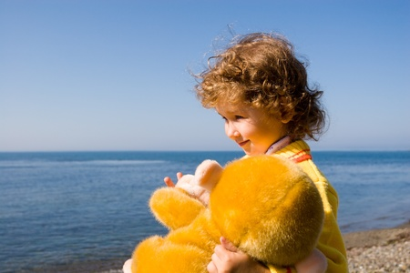 curly headed: The little girl looks at the sea, in a hand the toy monkey.