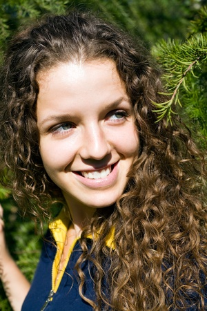 frizzy: The smiling girl on a background of a coniferous tree