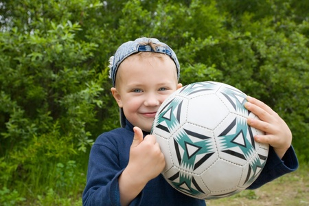The little boy holds a football in hands. photo