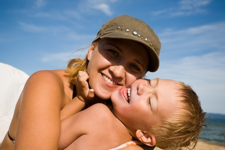 feels: Mother and the child (son) on a beach in summer day. Stock Photo