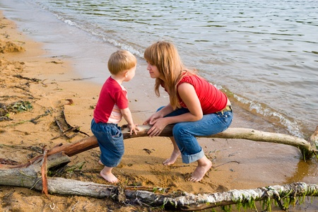 Mom and the son talk at the sea.Evening. photo