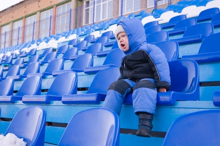 Little boy sits on a tribune and shouts. Stock Photo - 10531634