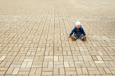 Little boy sits on a stone blocks. photo