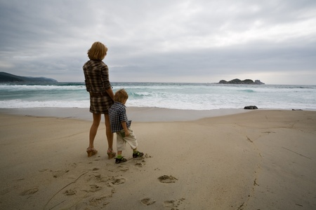 Storm on the sea.Mother and the son on a deserted beach.Mother specifies a hand island. photo