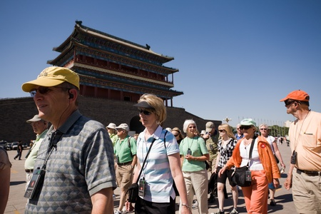 BEIJING, CHINA - JUNE 02: Group tourists walking on the Tiananmen Square. Tiananmen Square - the main area of China and the biggest in the world. On a background a Front Gate(Qianmen) of the inner city wall. June 02, 2009 in Beijing, China.