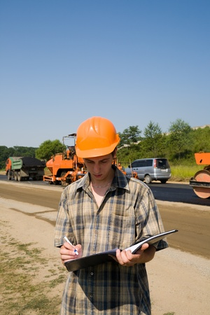 Road inspector on a working platform. Stacking of new asphalt. photo