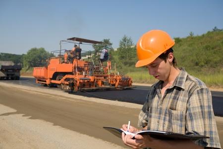 veiligheid bouw: Road inspecteur op een werkplatform. Stapelen van nieuw asfalt. Stockfoto