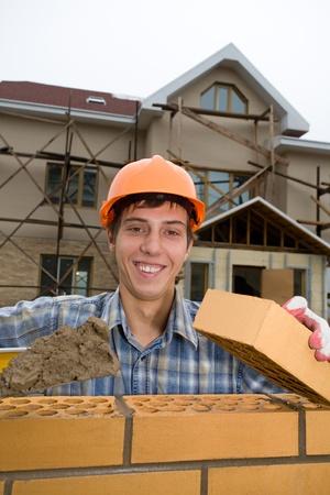 Mason builds a brick wall. Stock Photo - 10532110