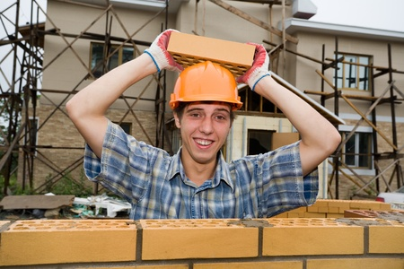 Young builder holds a brick on a helmet. Stock Photo - 10532022