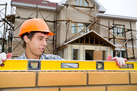 bricklayer: Mason construye un muro de ladrillo.