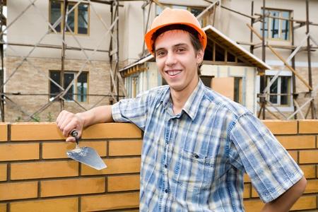 Mason builds a brick wall. photo