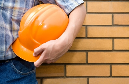 construction level: Bricklayer on a background of a brick wall. Stock Photo