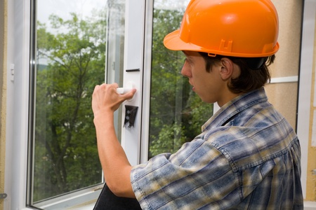 muscular build: Building inspector checks quality of installation of new windows.