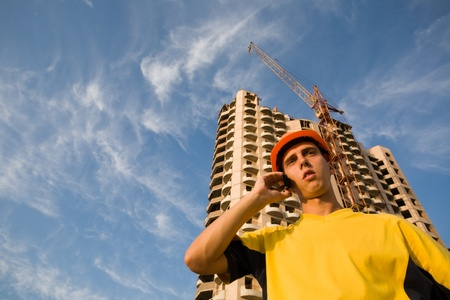 Builder inspector talks on mobile on a background of a builded building. photo