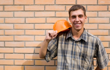 Bricklayer on a background of a new brick wall. photo