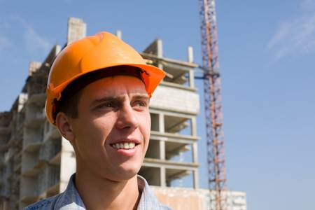 Young builder on a background of building object. photo