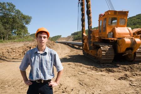 cilindro de gas: Joven ingeniero en una plataforma de trabajo en apilar un nuevo oleoducto. Foto de archivo