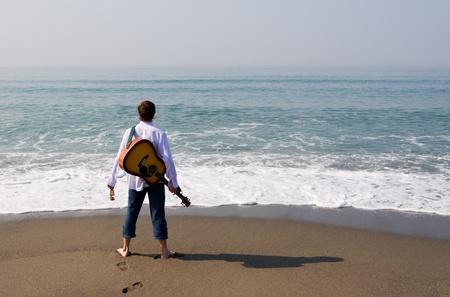 jeune mec: Le jeune homme (musicien) marche sur une plage avec une guitare.