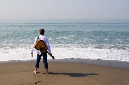 The young guy (musician) walks on a beach with a guitar. Stock Photo