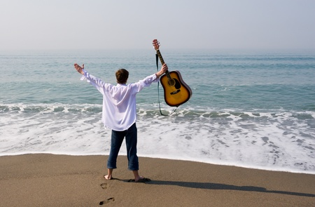 soloist: The young guy (musician) walks on a beach with a guitar. Stock Photo