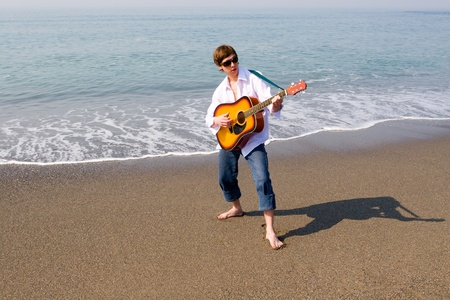 The young man(musician) plays on a guitar on sea coast. photo