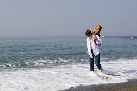 The young guy (musician) walks on a beach with a guitar. photo