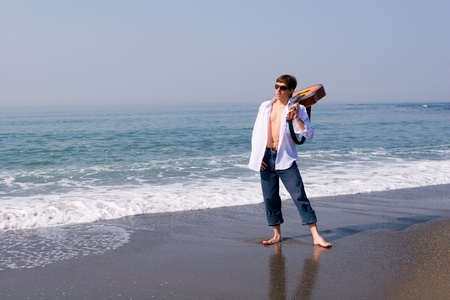 The young guy (musician) walks on a beach with a guitar. Stock Photo - 10575447