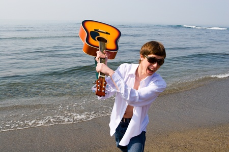 Musician shouts and swings a guitar. Stock Photo - 10546653