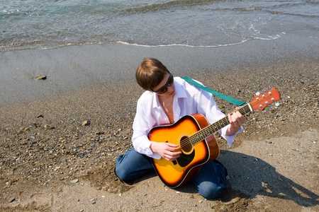 Young man(musician) plays on a guitar on sea coast. photo